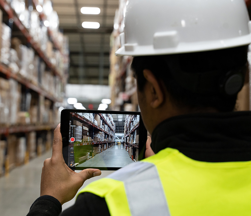 Man using a tablet to communicate in a warehouse